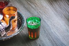 Moroccan traditional Tea table. Close up of a moroccan glass of tea on a wooden table Royalty Free Stock Image