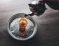 Moroccan traditional Tea table. Close up of moroccan traditional tea pot and glass on a silver plate Stock Photos