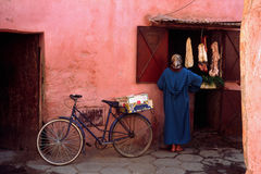 Moroccan woman at butcher. Woman with scarf and long dress at window in pink wall buying meat Stock Photography
