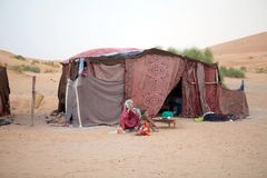 Moroccan woman and child. Morocco, Erg Chebbi, Berber camp:woman and child with the Berber traditional tent in the background. Erg Chebbi is of Morocco's two Royalty Free Stock Images