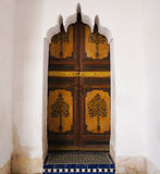 Moroccan wooden painted door set inside a carved plaster doorway Royalty Free Stock Images