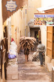 Moroccan worker carrying camel hides to the tannery. On a narrow alley