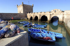 Morocco, Essaouira: fishing boats. Blue water and blue sky framed by a ancient stone fortress stock images