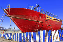 Morocco, Essaouira: fishing boats. Morocco, Essaouira: blue sky and red fishing boat resting near a blue and white barrier royalty free stock image