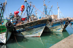 Morocco, Essaouira: fishing boats. Morocco, Essaouira: blue and green fishing boats , blue sky and green water stock images
