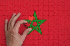 Morocco flag is depicted on a puzzle, which the man`s hand completes to fold.  stock illustration