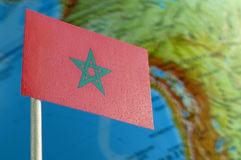 Morocco flag with a globe map as a background. Macro royalty free stock photography