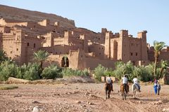 Morocco Fortified city of Ait Benhaddou. Fortified city of Ait Benhaddou, Morocco: men and horses are riding on the wadi near the fortified village Royalty Free Stock Images