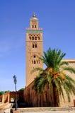 Morocco, Marrakesh: the Koutoubia. Morocco, Marrakesh: view of the Koutoubia with a palm tree stock photos