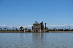 Morocco, Marrakesh, Menara Pavilion garden with snow atlas mountain behind. Morocco, Marrakesh, Menara Pavilion and Gardens reflected on the lake in late Stock Photos