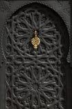 Morocco Marrakesh typical old black arabesque door. Morocco Marrakesh typical old arabesque black wooden door with brass door-knock Royalty Free Stock Images