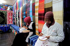 Two Berber women are working in colorful souk fabrics in Morocco. Morocco is one of the countries where famous carpets are produced Royalty Free Stock Images
