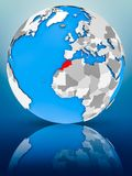 Morocco on political globe. Morocco on globe reflecting on surface. 3D illustration stock images