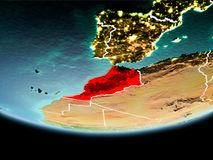 Morocco in red in the evening. Country of Morocco in red on planet Earth in the evening with visible border lines and city lights. 3D illustration. Elements of royalty free stock photos