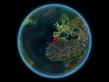Morocco on planet Earth from space at night. Morocco in red with visible country borders and city lights from space at night. 3D illustration. Elements of this royalty free stock photo