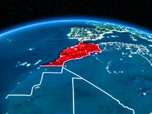 Morocco from space at night. Orbit view of Morocco highlighted in red with visible borderlines and city lights on planet Earth at night. 3D illustration royalty free stock photos