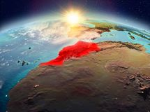 Morocco from space in sunrise. Satellite view of Morocco highlighted in red on planet Earth with clouds during sunrise. 3D illustration. Elements of this image royalty free stock photography