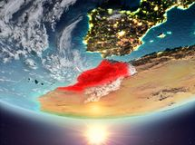 Morocco with sun. Morocco during sunrise highlighted in red on planet Earth with clouds. 3D illustration. Elements of this image furnished by NASA Royalty Free Stock Photography
