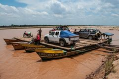 Vehicles embark on barges to cross the river. Morondava, Madagascar - nov 8 2016 : off-road vehicles embark on barges to cross the Tsiribihina river. Effective stock photo