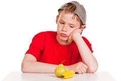 Morose young boy staring at a ripe banana and pear. Morose young boy sitting at a table staring at a ripe banana and pear with a glum expression, conceptual of a Stock Photos