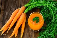 Morotfruktsaft i exponeringsglas och grönsaker beside Royaltyfri Fotografi