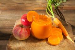 Morotfruktsaft i exponeringsglas på tabellen Arkivfoton