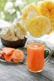 Morotfruktsaft i kanna och exponeringsglas av genomskinligt exponeringsglas på en bakgrund av rosor Arkivbild
