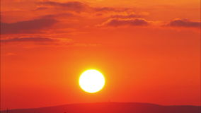 Morotsfärgad solnedgång med solen, tidschackningsperiod Arkivfoto