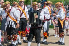Morris dancer playing accordion with troupe in background stock photo