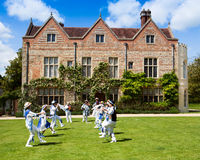 Morris dancers in front of Greys Court. Traditional Morris dancers performing on the lawn in front of Greys Court Tudor Country House Stock Photo