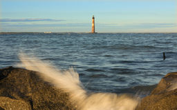 Morris island lighthouse. Lighthouse in the sea with waves crashing over rocks Royalty Free Stock Photo