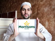 Morrisons Supermarkets chain logo. Logo of Morrisons Supermarkets chain on samsung tablet holded by arab muslim man.  Morrisons, is the fourth largest chain of Stock Photo