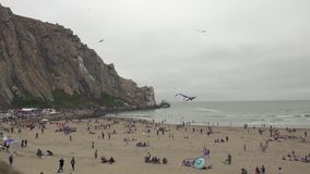 Weekend at Morro Bay. People on the Beach, and Beautiful Morro Rock. Morro Bay, California. People Gathered on the Beach to Celebrate Annual Morro Bay Kite stock footage
