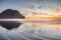Morro-Buchtfelsen und -strand am Sonnenuntergangabend Stockfotografie