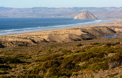 Morro Rock at Morro Bay. View of the Morro Rock from Montana De Oro State Park including sand dunes, pacific ocean and greenery stock photo