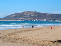 Morrocan beach in Agadir. Beautiful beach in Agadir in February, three Arabic words on the northwest of Mount Agadir, meaning God, King and Nation, Morocco Stock Photography