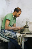 Morrocan man shapes pottery as it turns on a wheel in Fes Royalty Free Stock Images