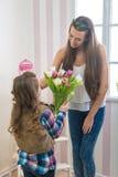 Mors dag - flickan ger hennes mamma en stor bukett av tulpan som trycker på Royaltyfri Fotografi