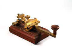 Morse key. Old brass telegraph key on a wooden plate Royalty Free Stock Photo
