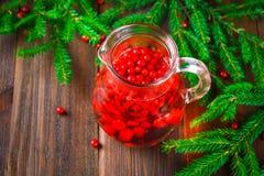 Morse ou o chá da airela em um jarro de vidro cercado pelo abeto ramificam em uma tabela de madeira Fotografia de Stock Royalty Free