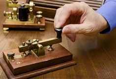 Morse Telegraph. A hand manipulating an old morse transmitter Royalty Free Stock Photo