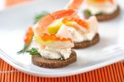 Morsels with prawns. Tidbits with prawns, spiced cream cheese, salmon caviar and dill Stock Photos