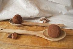 Morsi del cioccolato sull'cucchiai di legno Fotografia Stock
