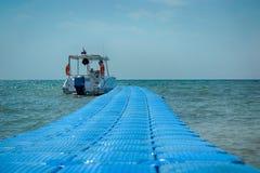 Morska łódź cumował z plastikowym błękitnym pontonowym mostem zdjęcia royalty free