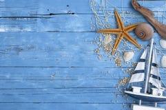 Morska dekoracja z skorupami, rozgwiazda, żeglowanie statek, sieć rybacka na błękita dryfu drewnie zdjęcia stock