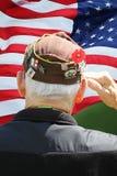 Morski weteran Salutuje przed flagą zdjęcia royalty free