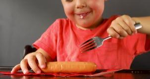 Morso di cibo del ragazzo sulla salsiccia dalla forcella del metallo video d archivio