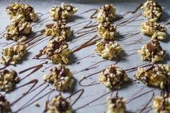 Morsures blanches d'énergie de chocolat alignées sur faire cuire le papier parcheminé photo stock