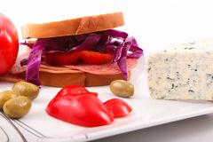 Luncheon Sandwich close up. Mortadella luncheon meat with blue cheese toast with olive, tomato and pepper as breakfast meal Royalty Free Stock Photography