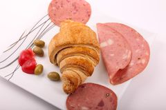 Luncheon and croissant. Mortadella luncheon meat with croissant, olive and tomato as breakfast Royalty Free Stock Photo